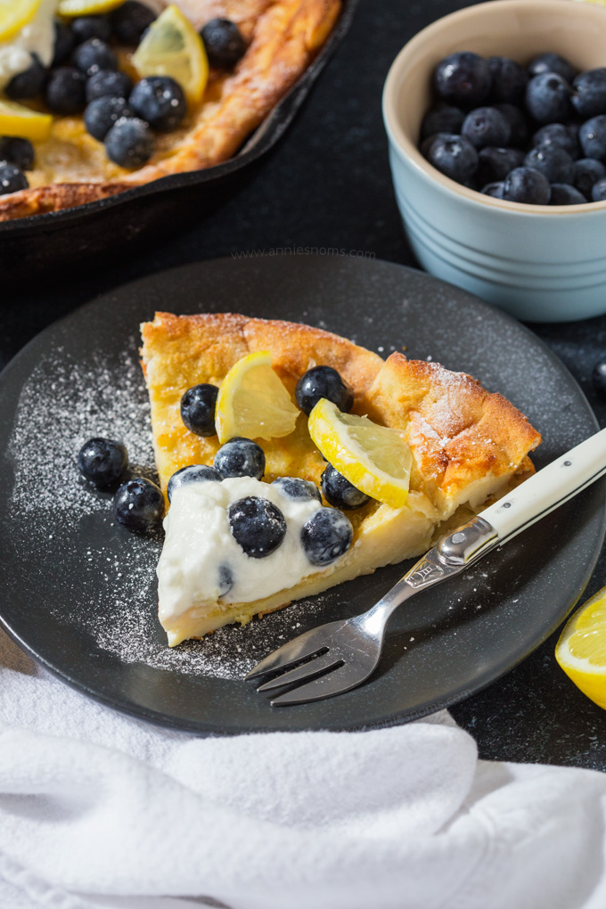 This light and fluffy Dutch Baby Pancake is infused with lemon and baked until golden. Topped with cream, blueberries and lemon it makes for a fab breakfast!