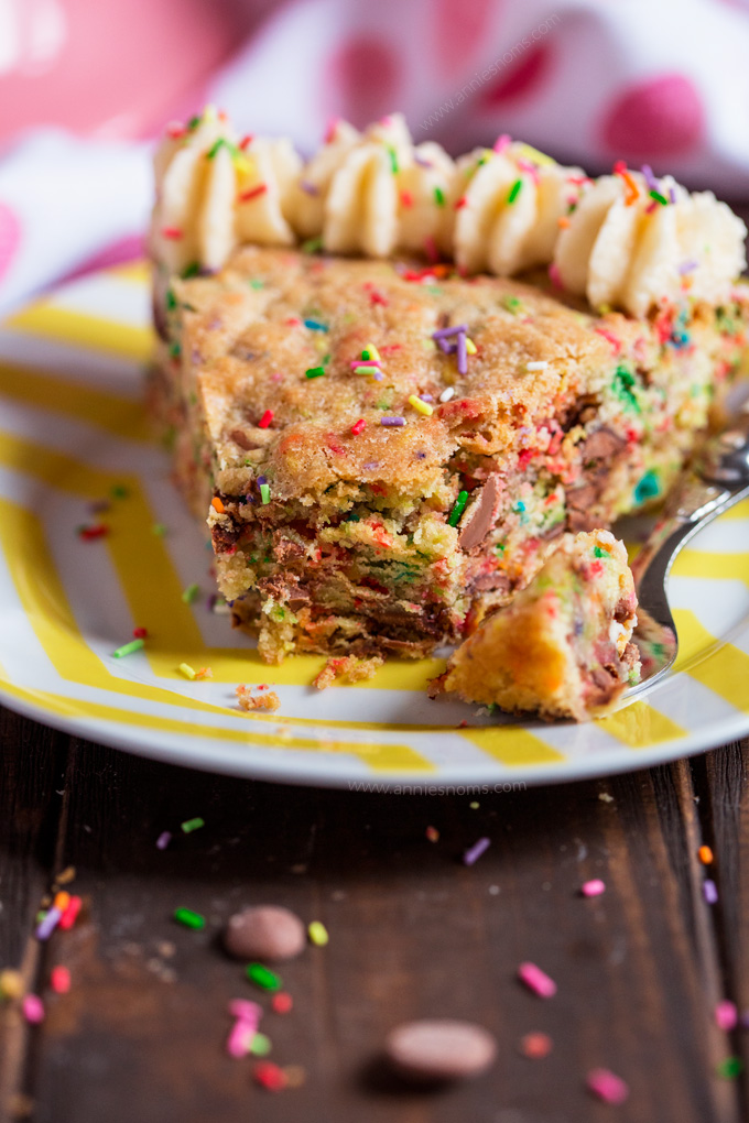 This thick and chewy cookie is filled with funfetti and milk chocolate chips and then baked in a cake pan to create a twist on traditional birthday cake! Decorated with buttercream and funfetti, it's a fantastic alternative to a bog standard cake!