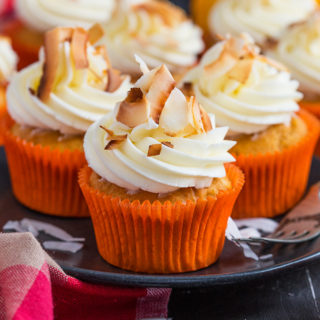 Earthy pumpkin cupcakes are given a tropical twist with coconut flakes and a creamy coconut frosting to make one seriously awesome hybrid treat with summer and autumn flavours!