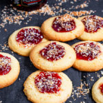 "These Vegan Strawberry Coconut Thumbprint Cookies are so easy to make and taste amazing! Toasted coconut tops strawberry jam and a ""buttery"", cookie to make one bitesize delicious treat!"